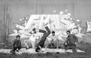 Graffiti mural promoting the Peace Train Breaking Competition, 1984-1985, Hartford, CT. Five boys and young men strike poses while breakdancing.