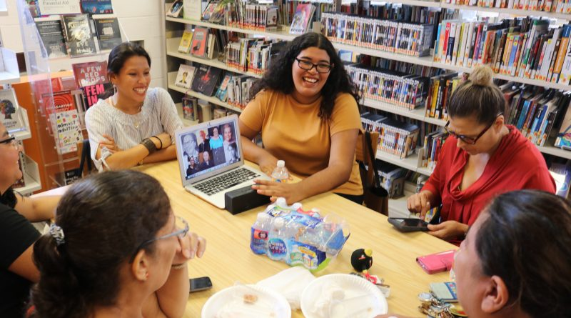Students sit around a table with community members who are sharing their stories of life in Hartford. They are at a library and surrounded by books on all sides.
