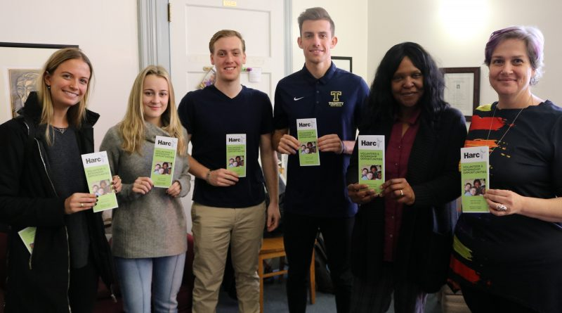 Four students (two women, two men) stand with their partner Marisely (from HARC) and Professor Leah Cassorla, holding the green brochures they made to advertise volunteer opportunities at HARC
