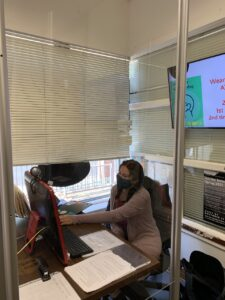 A student works at the front desk of Trinfo. The student is wearing a mask and there are pandemic protocols on a screen above.
